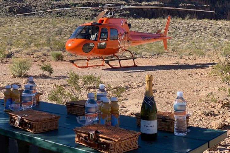 Grand Canyon All-American Helicopter Tour | After hotel pickup by limousine, enjoy a scenic flight to the West Rim, flying over Hoover Dam, and then land on a canyon bluff for a glass of Champagne and snacks.